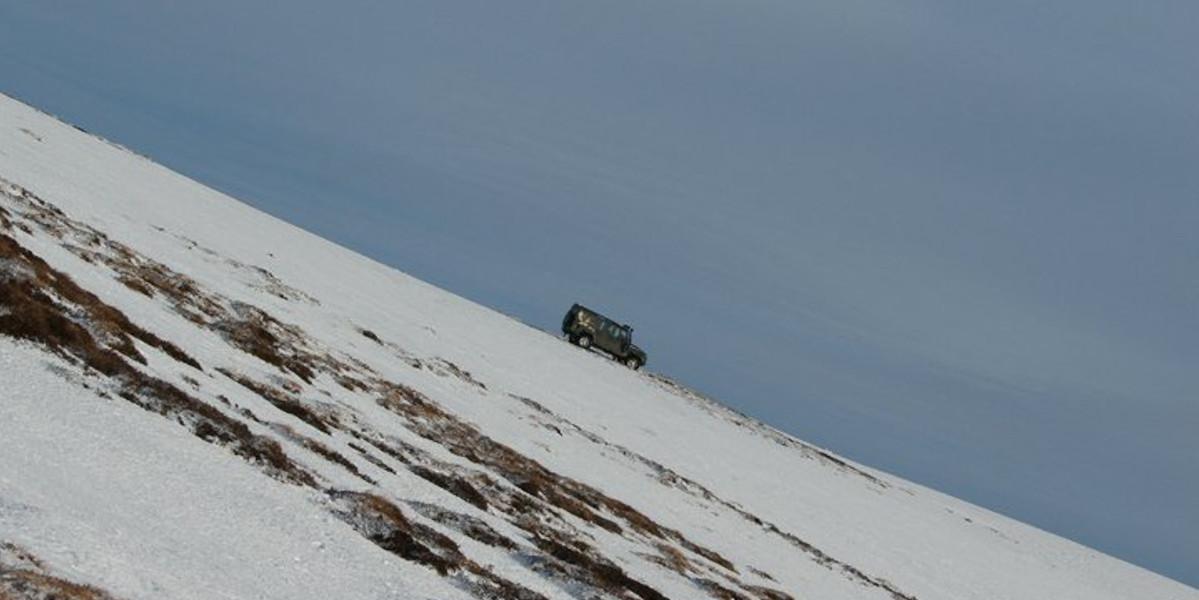 Landrover steiler verschneiter Hang abfahren
