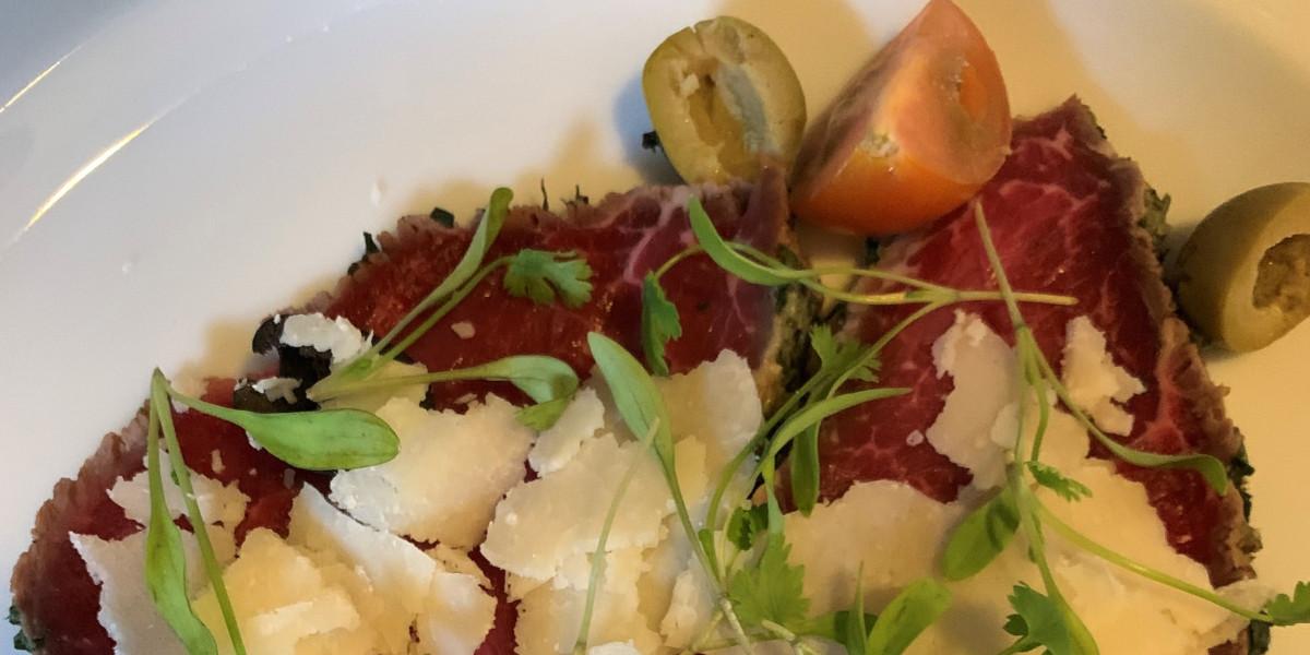 carne affettata su un piatto con olive, pomodori e contorno
