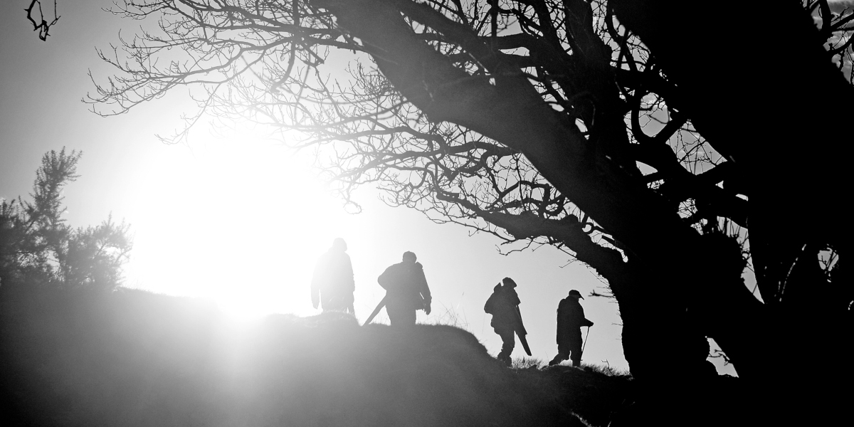 backlit black and white shooting party crossing ridge