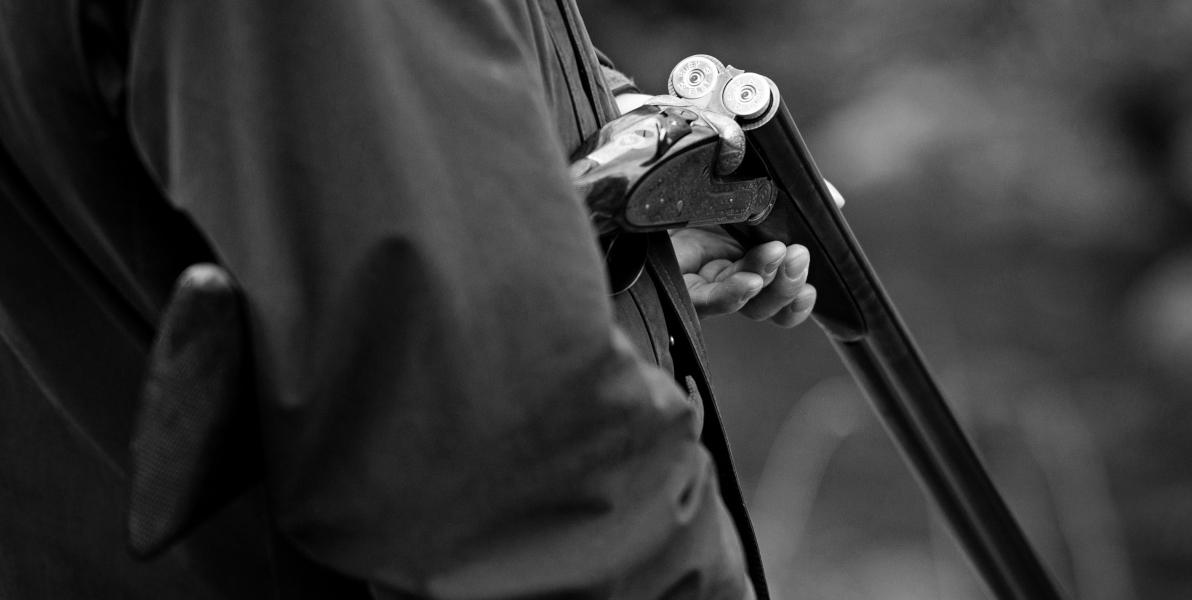 man holding open shotgun with cartridges black and white image