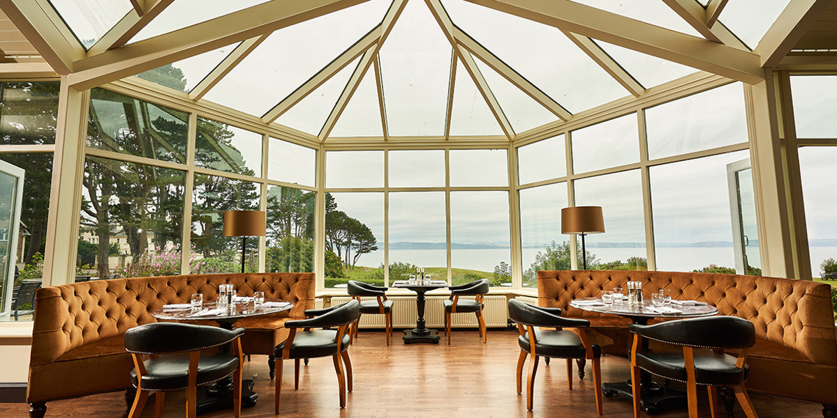 restaurant conservatory with two curved velvet sofas and tables
