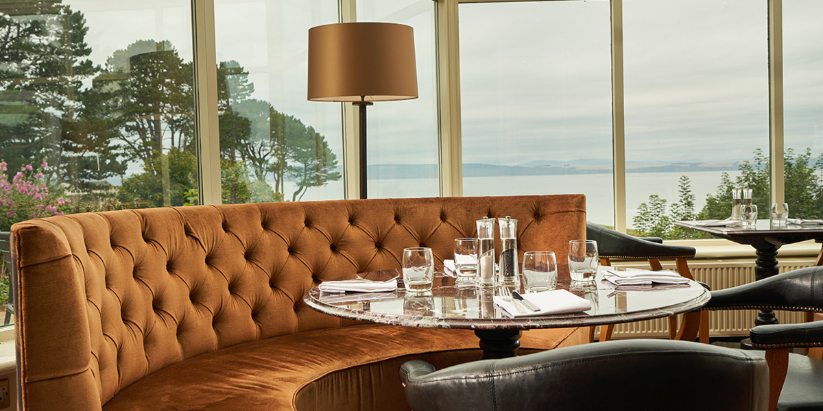 Restaurant with curved orange velvet seating looking out over the sea