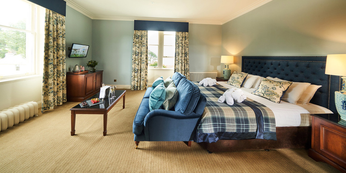 Large hotel room with superking bed and blue sofa with double aspect windows