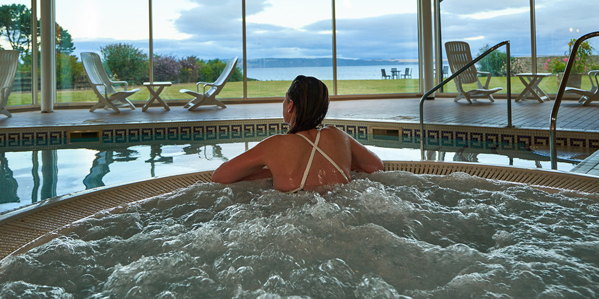 woman in jacuzzi beside indoor swimming pool with windows overlooking lawn and sea shore