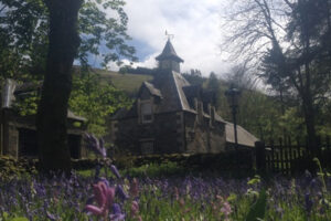 Bell tower in wood with bluebells in foreground