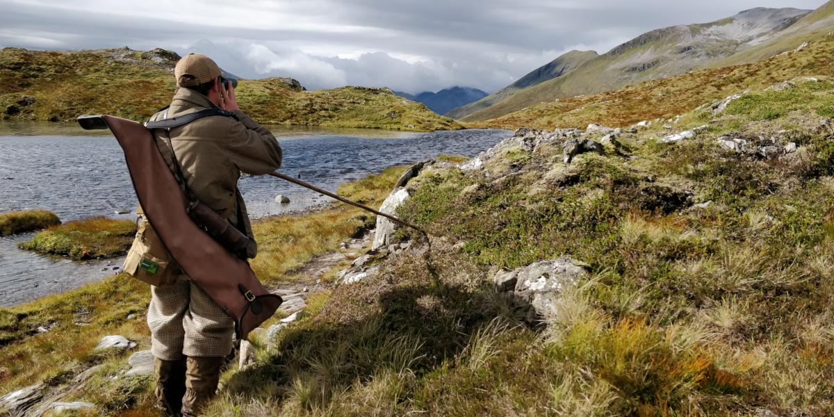 stalker on a hillside overlooking a loch
