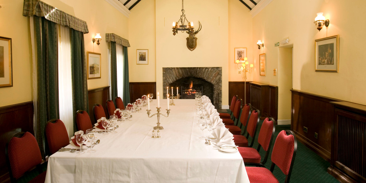 banqueting table with white linen, open fire and stags head on wall