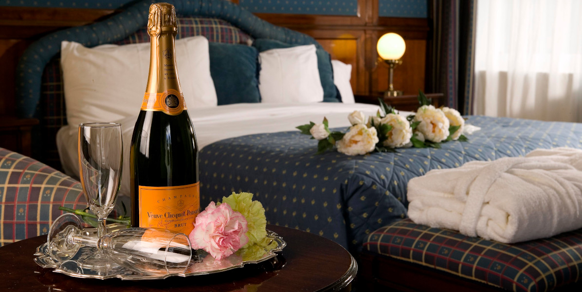 twin bedded hotel room with champagne bottle and blue and white linen