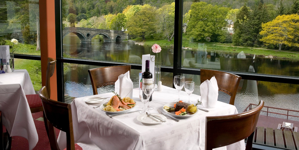 dining table with food and red wine, single pink carnation overlooking river tay