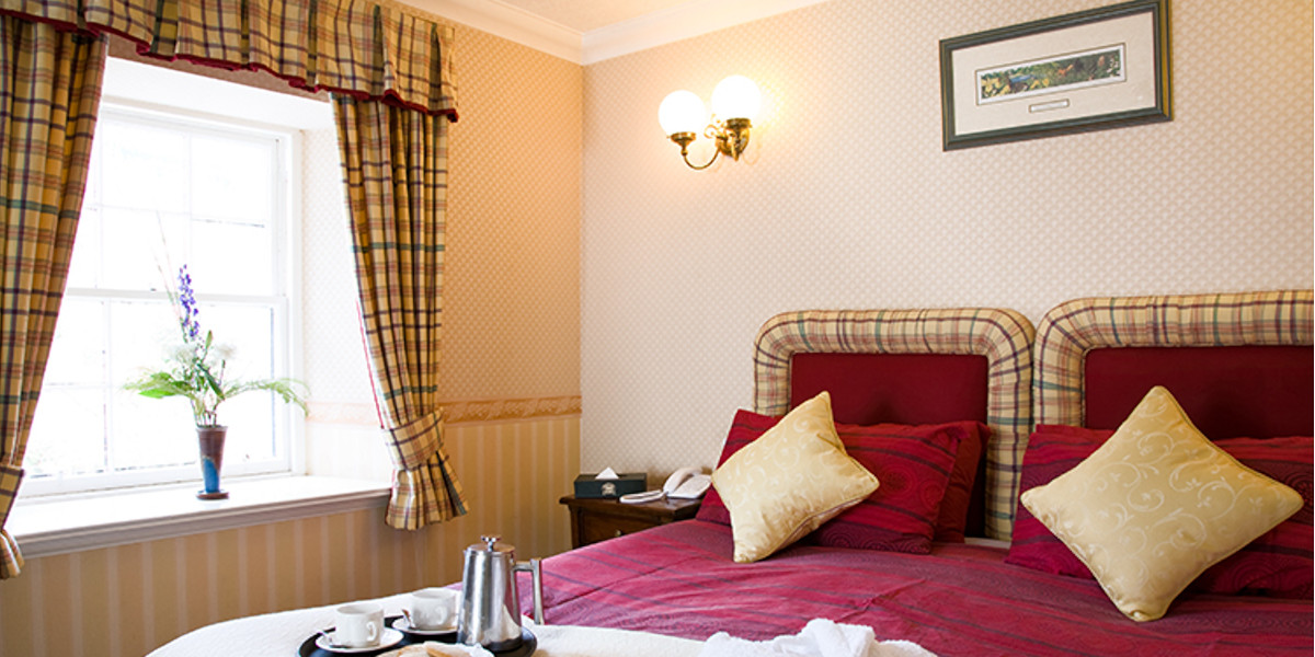Double bedded hotel room with tartan curtains and red linen