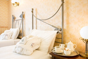 Twin bedded hotel room with creamlinen and toweling slippers and dressing gown