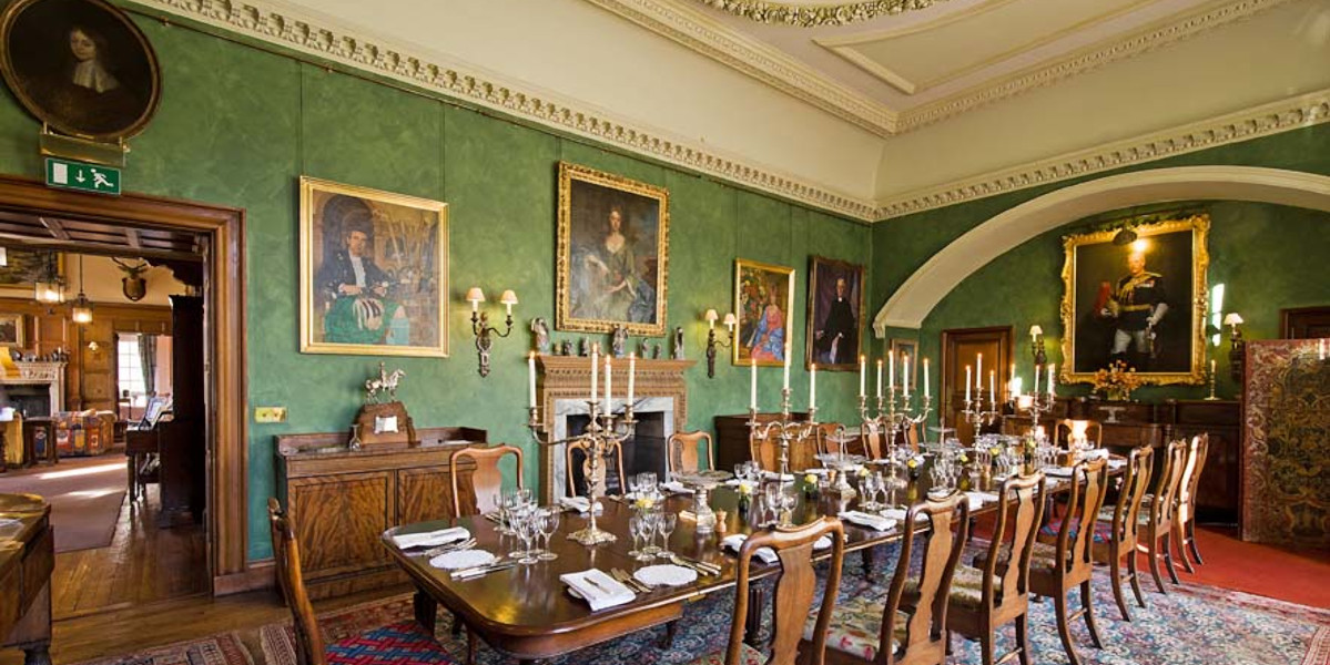 Scottish castle dining room with paintings on walls and candelabra on table