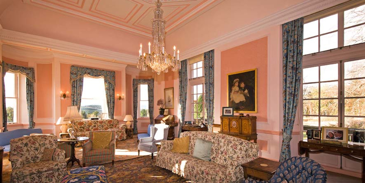 pink coloured Scottish castle drawing room with art and sofas