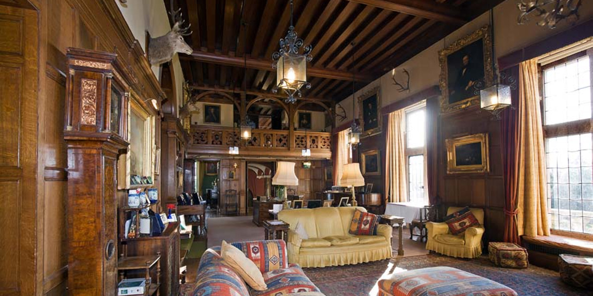 Castle sitting room withe sofas stags head and gallery