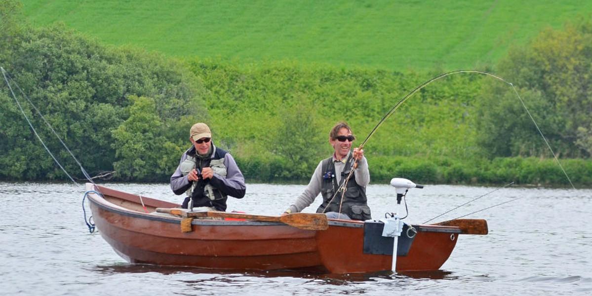 deux pêcheurs à la mouche dans un bateau combattant un poisson