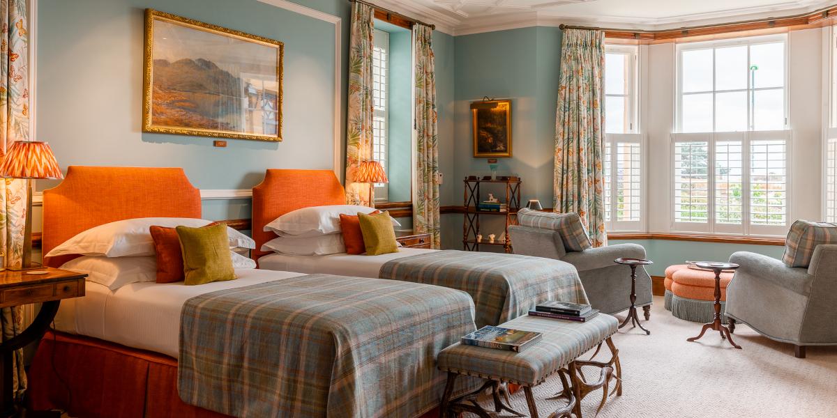 Chambre d'hôtel à deux lits avec têtes de lit orange et décoration murale bleue