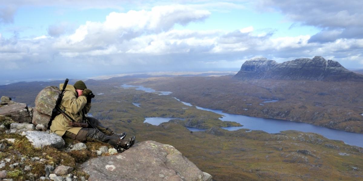 Traqueur de cerfs au sommet d'une montagne à la montagne Suilven deer en arrière-plan