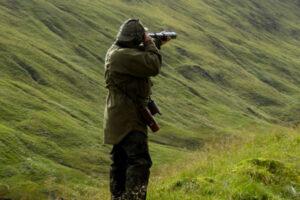 Deer s talker dressed in green with telescope spying hillside for deer