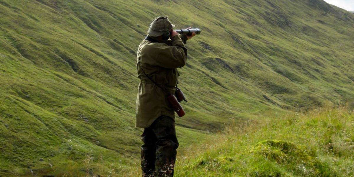 Deer s talker vêtu de vert avec un télescope espionnage de la colline pour le cerf