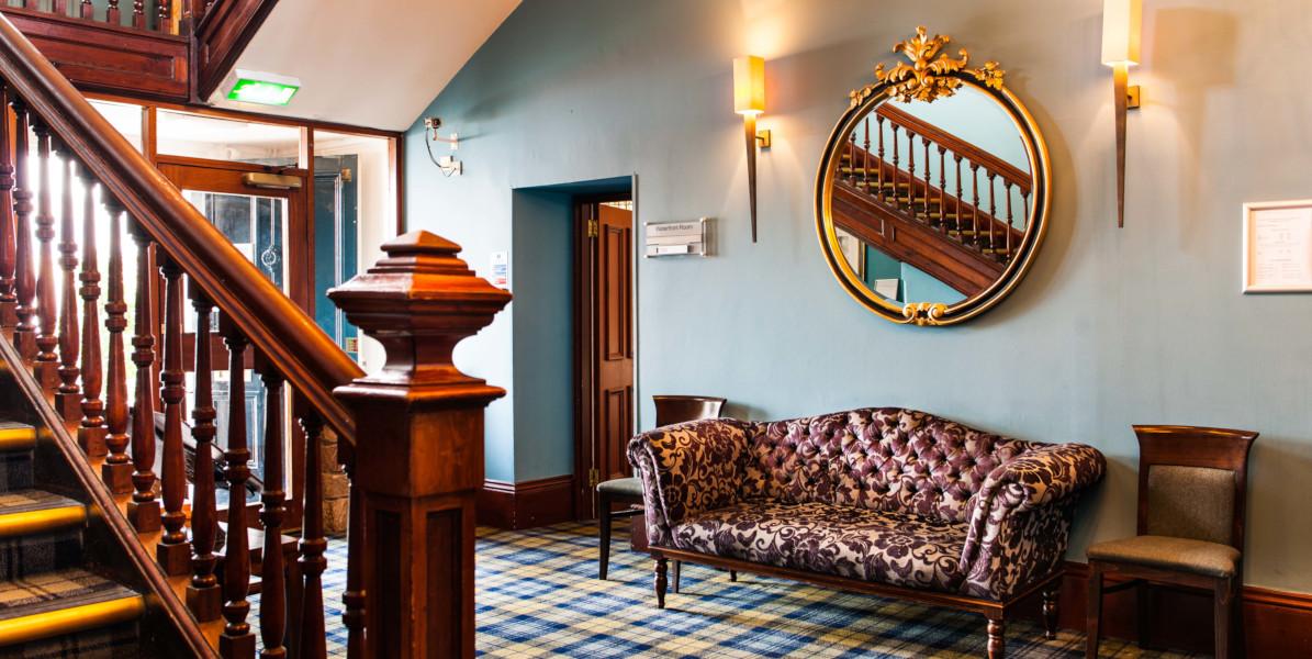 Hotelhalle und Treppe mit blau-gelbem Tartan-Teppich und dunkler Holztreppe