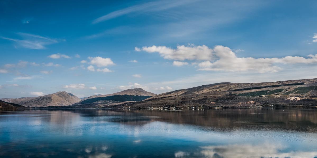 Schottischer Seeblick mit Bergen und blauem Himmel