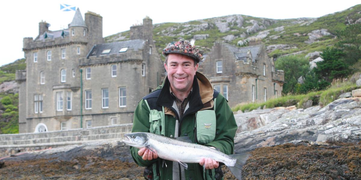 pêcheur avec grilse devant le château écossais