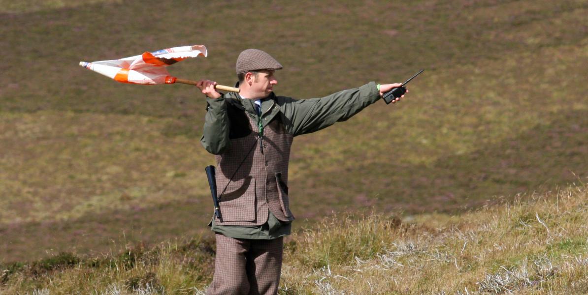 Batteur de tétras écossais avec drapeau pointant
