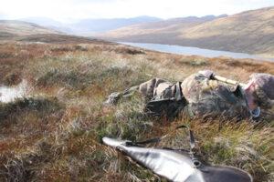 Scottish deer stalker prone spying deer