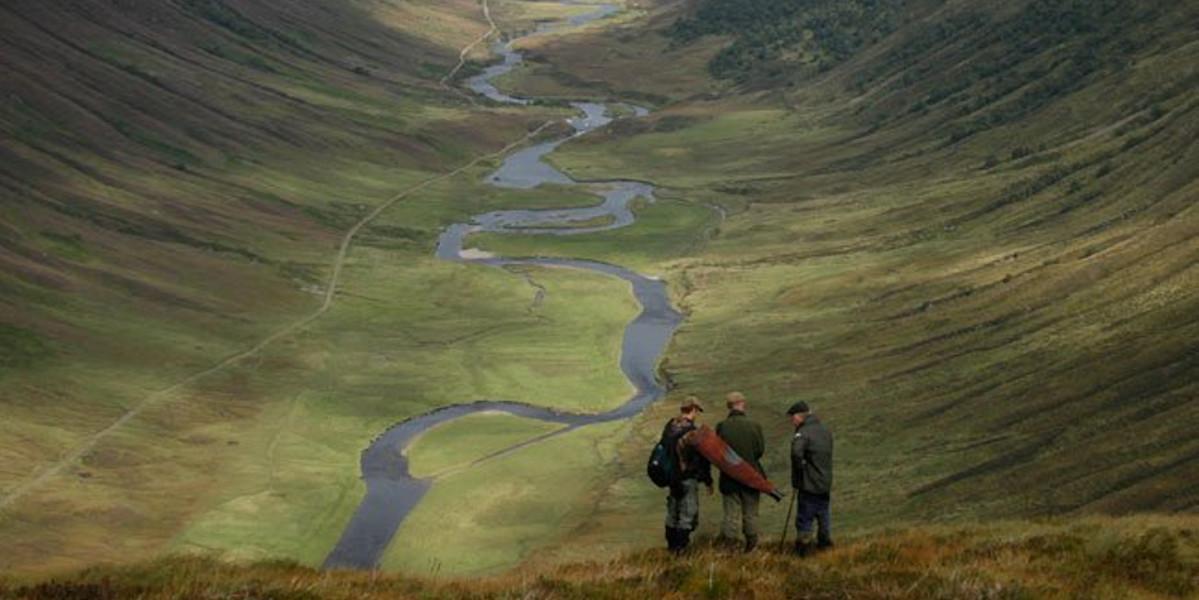 3 deer stalker sur colline au-dessus de la vallée écossaise