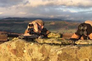2 deer stalkers hiding behind large rock using binoculars