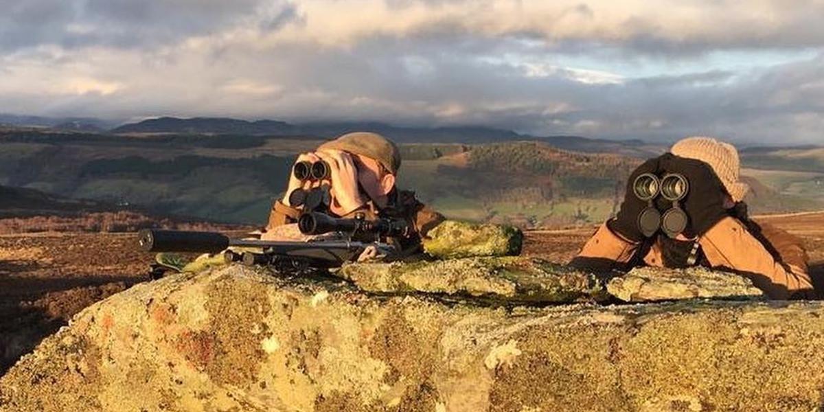 2 harceleurs de cerfs se cachant derrière un gros rocher à l'aide de jumelles