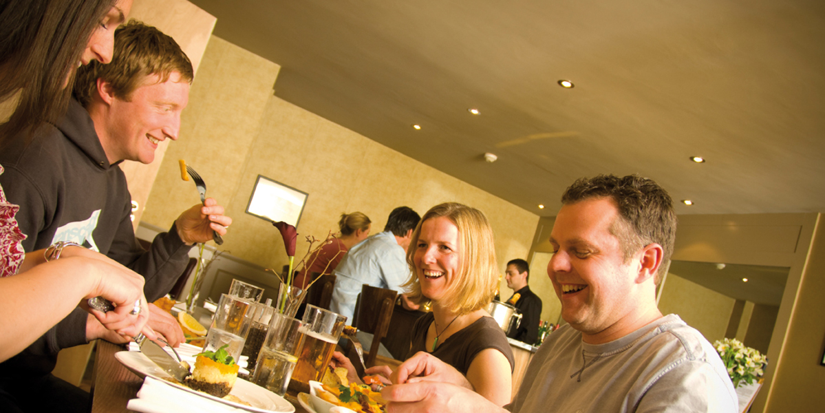 two couples eating at hotel dining table