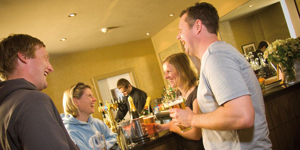 barman at bar with 2 couples having drinks