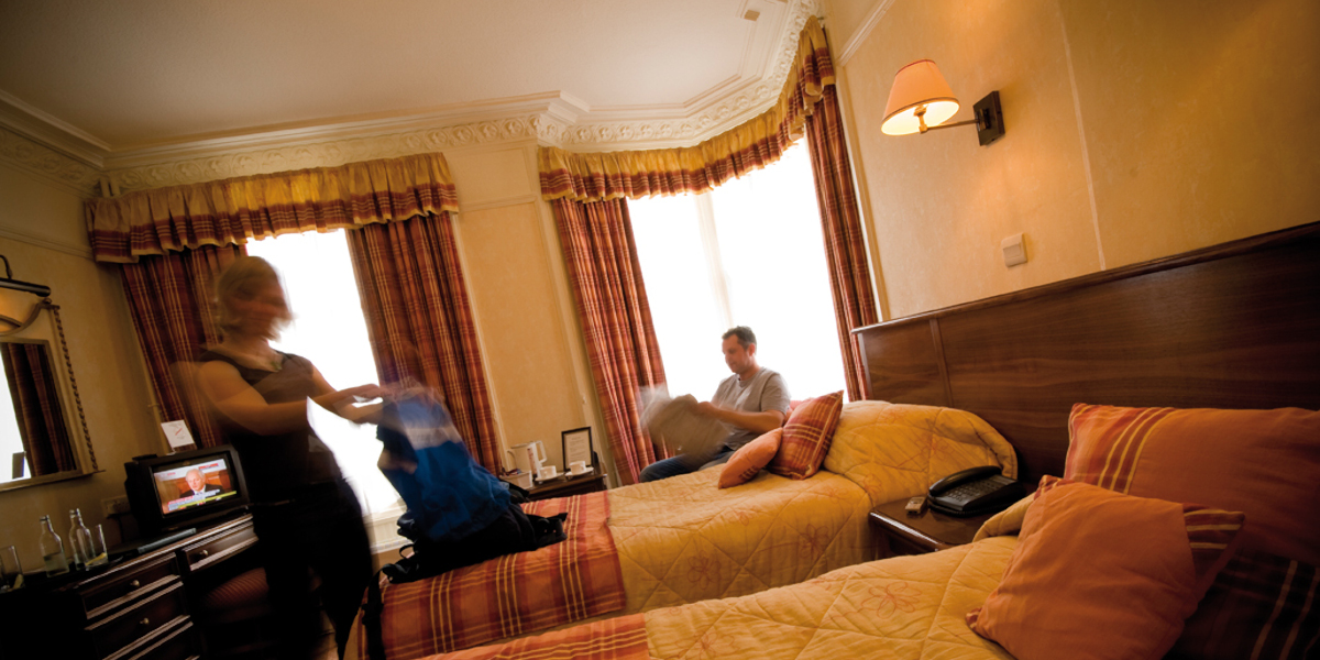 twin bedded hotel room with guests