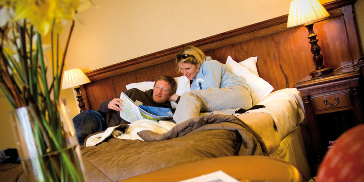 man and woman in hotel bedroom reading guide book