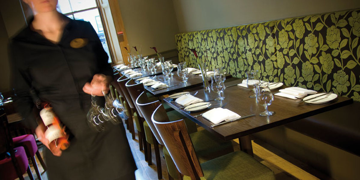 hotel bistro green bench seating along wall tables and chairs