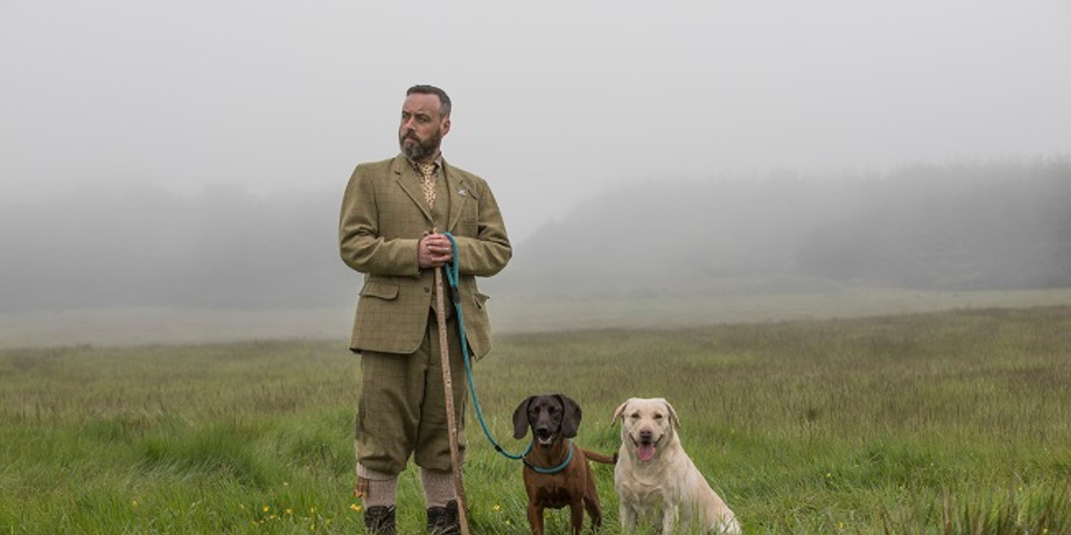 Game keeper in tweed with labrador and cocker