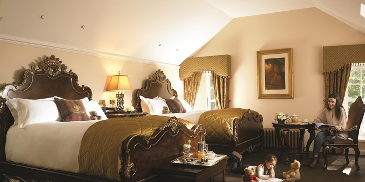 Luxury hotel room with 2 queen beds, woman and child