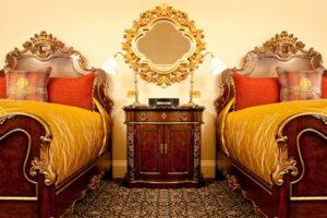 Camera d'albergo di lusso con letti gemelli e comodino, biancheria color oro e arancione