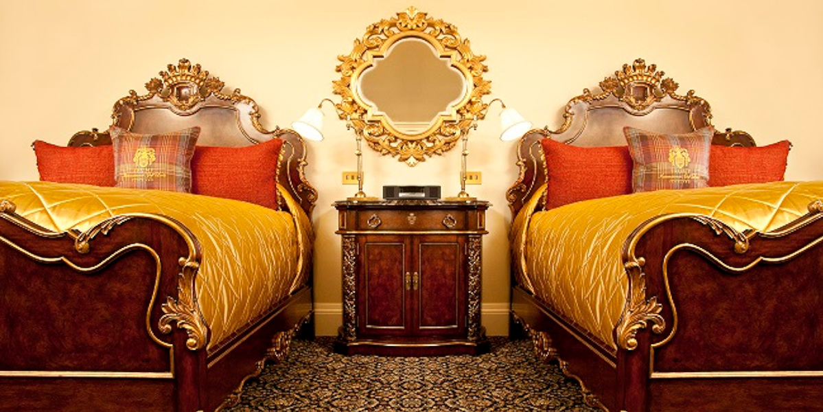 Luxury hotel room with twin beds and bedside cabinet, gold and orange linen