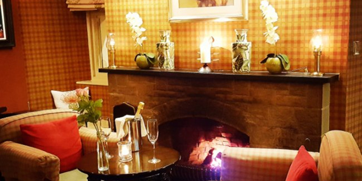 lit open fire with table and two chairs champagne and 2 glasses
