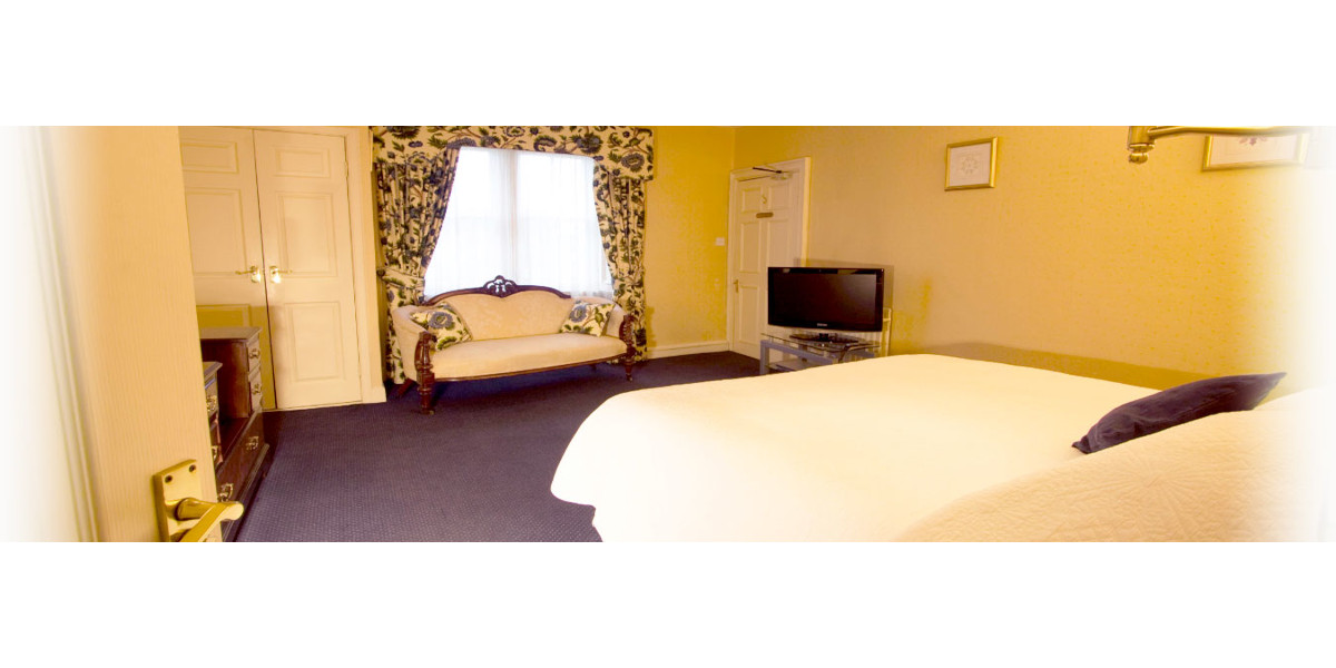 hotel double bedroom with sofa and yellow decoration accents