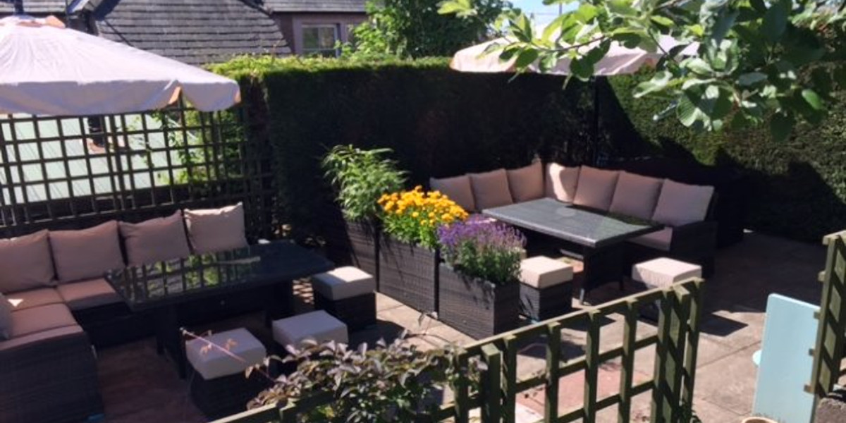 hotel beer garden with rattan effect tables and seat with pink cusions