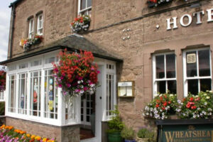 exterior of red sandstone built hotel with flowering baskets and tubs