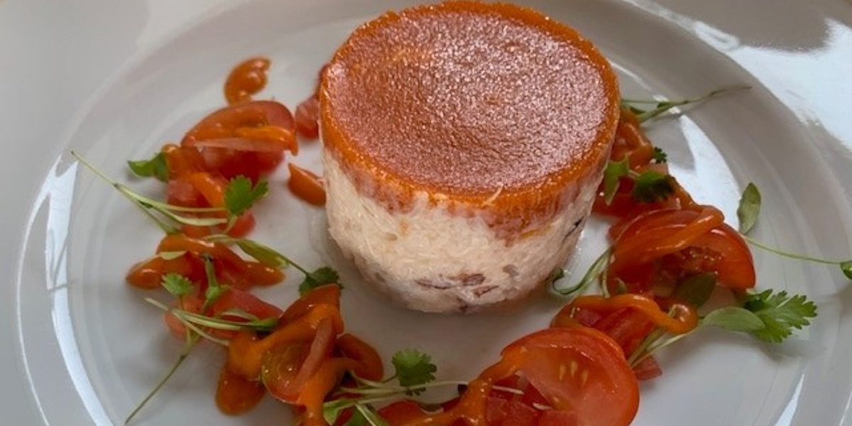 crab and tomato dish on a white plate