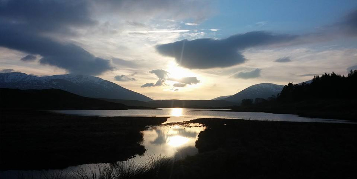 sunset over Scottish loch and mountains