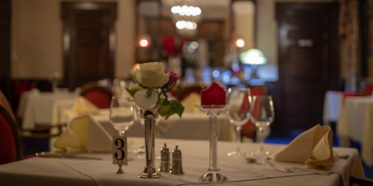 restaurant table with white linen red and white roses and wine glasses