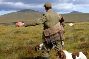gamekeeper with dog on hillside