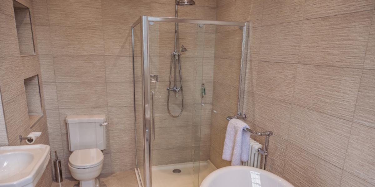 Ducha y baño con suelo de baldosas beige.