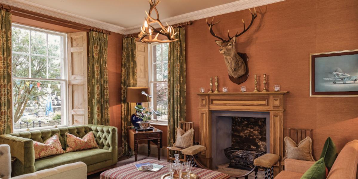 salón con chimenea de cabeza de ciervo y ventanas de doble aspecto con cortinas verdes